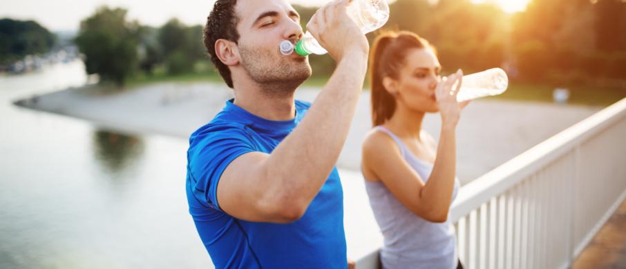Two people drinking water bottles